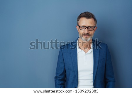 Serious businessman wearing glasses staring intently at the camera with a focused expression against a blue studio background with copy space