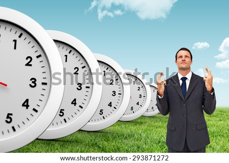 Serious businessman with fingers crossed is looking up against blue sky over green field