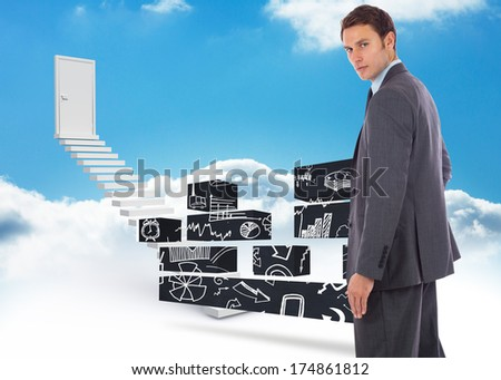Serious businessman with hand on hip against steps leading to closed door in the sky