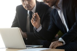 Serious businessmen in suits talk work together with laptop, financial advisor consulting convincing client about online investment benefits concept, make business offer with computer, close up view