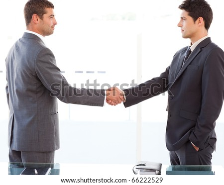 Serious businessmen shaking their hands after a meeting at the office
