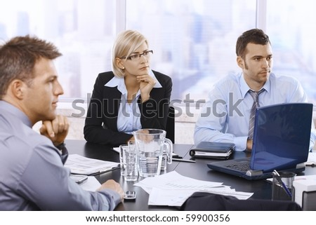 Serious businesspeople focusing on work in office, looking at colleagues out of frame.?