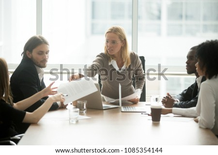 Serious businesswoman handing paper giving report or new marketing sales business plan to employee at diverse team meeting, female boss discussing work result at corporate group briefing in boardroom