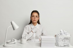 Serious businesswoman has long dark hair, wears round spectacles and white shirt with gloves, looks directly at camera, sits in coworking space with pile of papers, isolated over white background