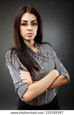Serious businesswoman holding her arms crossed in closeup pose on gray background