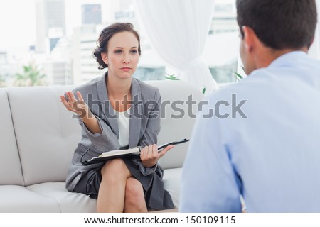 Serious businesswoman talking to her colleague in cosy bright office