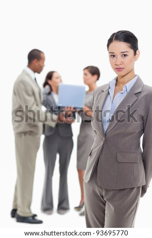 Serious businesswoman with co-workers talking with a laptop in the background