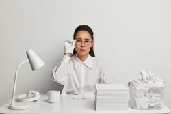 Serious businesswoman works at office desk, sits at white desk with pile of papers, drinks coffee, wears neat clothes, tries to make serious decision, has mysterious look. Monochrome shot, one tone