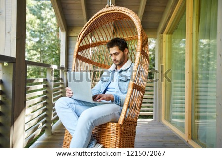 Serious busy young male freelancer in denim jacket sitting in wicker armchair and using laptop while browsing Internet on balcony of cottage house