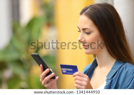 Serious buyer buys on line with credit card and smart phone in a colorful street