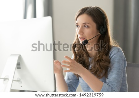 Serious call center operator in wireless headset talking with customer, woman in headphones with microphone consulting client on phone in customer support service, looking at computer screen close up