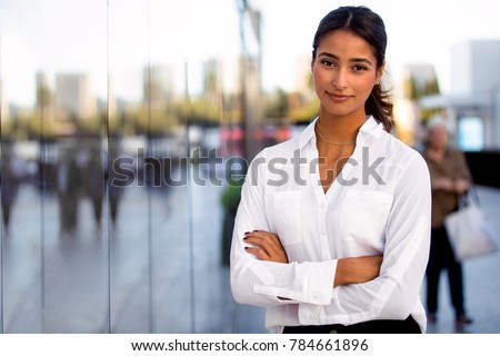 Serious career motivated successful female business professional standing proud and confident near downtown financial buildings