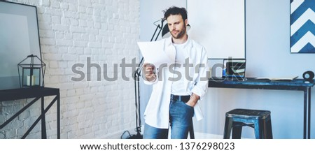 Serious casually dressed caucasian entrepreneur reading information from paper standing in modern interior coworking space, confident businessman checking report during working process in office