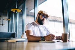 Serious caucasian bearded male author in eyewear for vision correction writing in notepad working on freelance in cafe interior, pensive mature man making notes of ideas and plans during free time