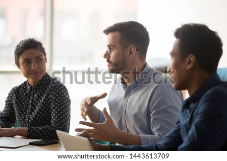 Serious caucasian business man manager talk meeting indian african people work group sit at conference table, diverse team listen to coach mentor boss consult clients at corporate office briefing