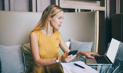 Serious caucasian businesswoman using mobile phone for confirming online shopping sitting in modern interior, prosperous manager checking notification about transaction on freelance job