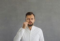 Serious caucasian man demonstrates a gesture of silence standing on a gray concrete background. Man pretends to close his mouth with a zipper promising to keep a secret. Concept of secrecy and silence