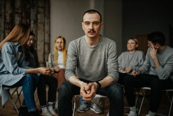serious caucasian man, member of alcoholics anonymous club sit in center of isolated room. people support each other in the background, sit in the circle. help, support, problem, psychotherapy