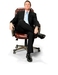 Serious Caucasian man with short black hair in business formal outfit with hands holding leg - Isolated