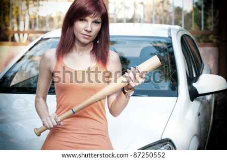 Serious caucasian redheaded woman standing by the car with a baseball bat