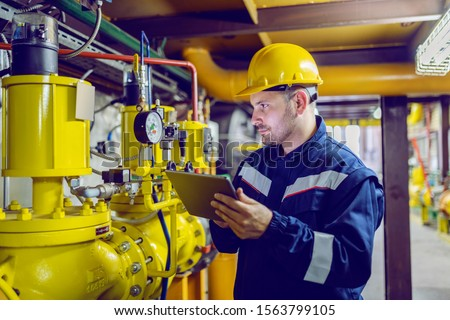 Serious caucasian unshaven worker in protective uniform and with hardhat using tablet for checking temperature in pipes. Factory interior.