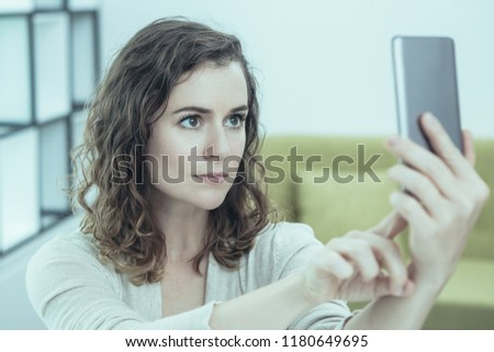 Serious Caucasian woman holding smartphone and taking selfie at home. Young lady taking picture for profile. Communication concept #1180649695