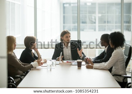 Serious ceo leading corporate team meeting talking to multi-ethnic employees giving instructions, confident boss speaking to diverse workers group at briefing delegating work explaining new project