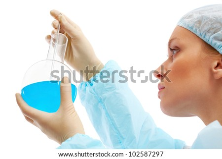 Serious clinician looking at blue liquid in flask during medical test