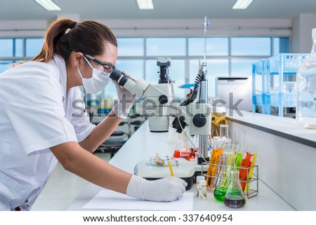 Serious clinician studying chemical element on tester and lecture in laboratory