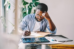 Serious competitive african american hipster guy puzzled on doing homework task sitting at desktop, creative thoughtful dark skinned male designer concentrated on making sketch and planning
