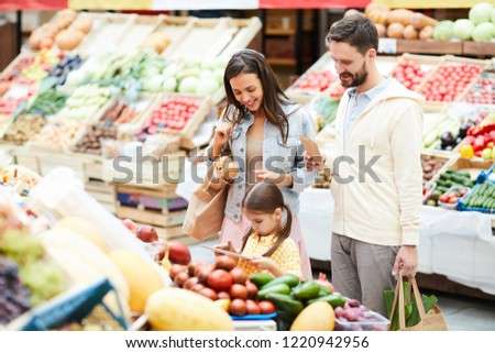 Serious concentrated little daughter with pony tails standing at food shelves and scanning price tag using tablet in food store, cheerful parents looking at tablet screen while making purchases