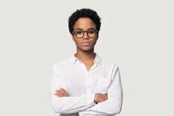 Serious concentrated young african american girl in eyeglasses standing with folded hands, headshot studio portrait. Focused black female professional looking at camera, isolated on grey background.