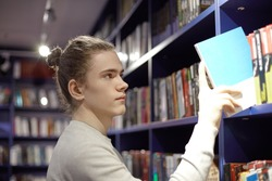 Serious concentrated young European man with hair bun taking book from bookshelf in bookstore while searching for popular bestseller. 20 year old male choosing detective to read in his spare time