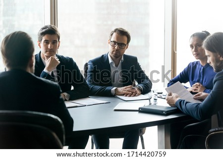 Serious confident businesspeople listening to mentor leader at meeting in boardroom, sitting at table at briefing, business partners colleagues discussing project strategy, contract terms
