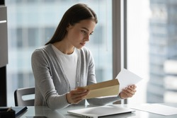 Serious confident businesswoman reading letter, holding open envelope, sitting at desk in modern office, received news or important information, young woman working with correspondence