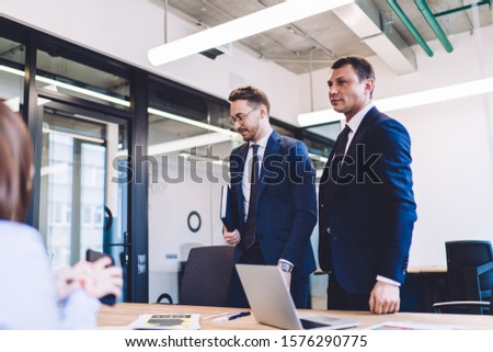 Serious confident executive man and male colleague with notebook standing together at table prepared for business meeting with coworkers in office