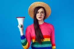 Serious confident lgbt activist leader girl in rainbow sweater holding in megaphone while standing against blue background