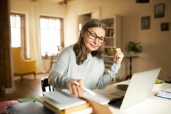 Serious confident middle aged female journalist with cup of coffee sitting at desk with books and laptop, making research, studying literature. Attractive mature woman copywriter working from home
