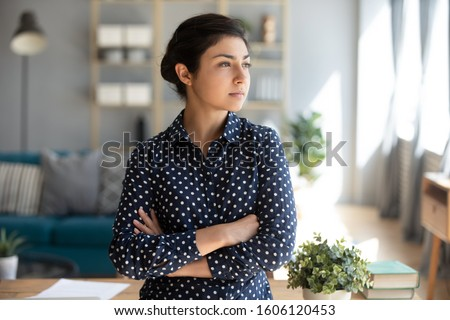 Serious confident young indian girl student professional look away forward to future dream of success at home office, thoughtful lady arm cross stand indoor think of entrepreneurship ambition concept
