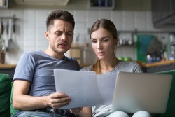 Serious confused couple checking high domestic bills with papers and laptop, millennial family discussing expenses or financial problems bankruptcy debt loan reading bad news in bank documents