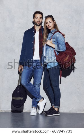 Serious couple in denim and jeans with luggage #609949733
