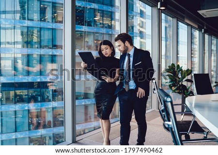 Serious coworking man and woman in elegant clothes walking along modern office and reading reports together while working on project