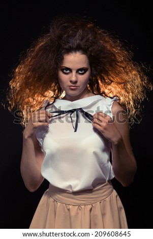 serious crazy woman with fluffy hair looking at camera. Toned image