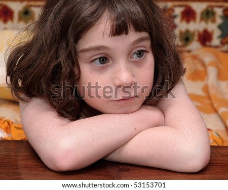Serious cute little girl rests her head on crossed arms close-up