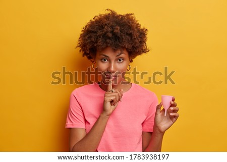 Serious dark skinned woman holds bell shaped menstruation cup for inserting in vagina, trapping menstrual fluid and leakage protection, tells secret information and tips how to use it, makes hush sign