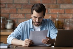 Serious distance employee analyzing statistics, data in paper financial reports at workplace with laptop. Focused young man reading document, loan agreement with payment schedule. Paperwork concept