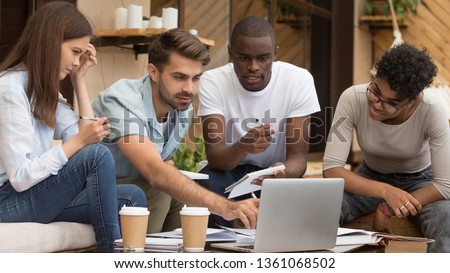 Serious diverse friends study together with laptop and notebooks prepare for exam in cafe, focused multiracial young people group talking using computer sitting on coffee house terrace doing research