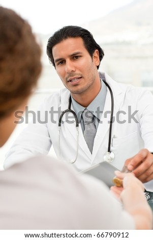 Serious doctor giving pills to his patient during an appointment in his office
