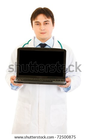 Serious  doctor holding laptop with blank screen in hands  isolated on white