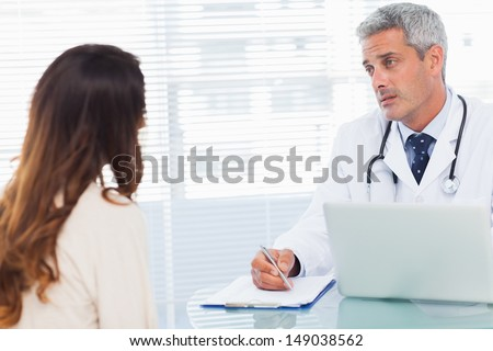 Serious doctor talking with his patient and writing on a notebook in medical office
